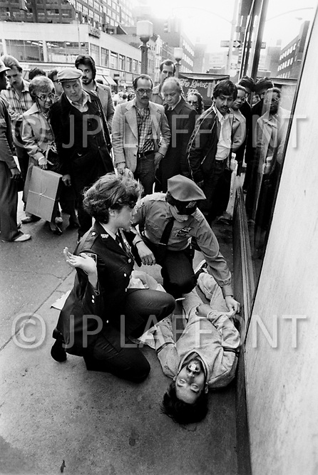 Manhattan, New York City, NY. May, 1980.<br /> Group of people watching how cop and lady deal with man lying on the street with an overdose. Times Square had acquired a reputation as a dangerous neighborhood during the 1980's.  The shabiness of the area, especially due its go-go bars, sex shops, and adult theaters, became an infamous symbol of the city's decline.