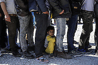 Pictured: A young boy rests on the ground amongst men who queue for food Friday 26 February 2016<br />Re: Hundreds of refugees have been given temporary shelter at the Stefanakis Army Camp in the Schisto area of Athens, Greece.