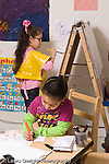 Education preschool 4 year olds art activity girl drawing and writing letters in foreground while girl paints at easel in background vertical