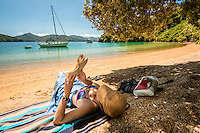 Young woman reading at Governors Bay in Marlborough Sounds, Nelson Region, Marlborough, South Island, New Zealand MR
