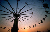 Silhouette shot of people on an amusement park ride.