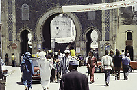 Bab Bousilout. La porte de la ville de Fès avec une groupe - Ouarzazate, Maroc - 1973<br /> <br /> Bab Bou Jeloud (also spelled Bab Boujeloud or Bab Boujloud) is an ornate city gate and the main western entrance to Fes el Bali, the old city of Fez. Traditionally and modern dressed people. A banner with a text in Arabic and the year 1973. Traffic signs.