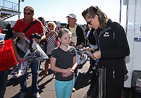 Feb. 23, 2013; Chandler, AZ, USA; NHRA top fuel dragster driver Leah Pruett signs autographs for a young female fan in the pits during qualifying for the Arizona Nationals at Firebird International Raceway. Mandatory Credit: Mark J. Rebilas-