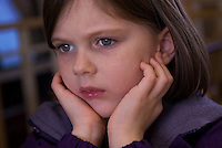 Young girl wears a worried look as she sits with her hands to her face.