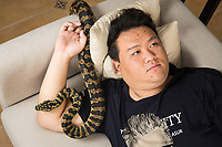 Huang Jiachen, 20, a snake collector and exotic species breeder with his pet python at home in Beijing. Huang set up a breeding farm for exotic species after collecting animals as a hobby and sells animals to China's pet markets. He also collects snakes from across the world, with a particular interest in vipers and pythons.