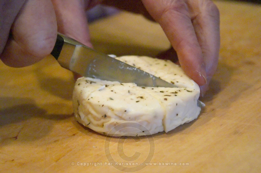 How to prepare French goat cheese (chevre) in herbs and olive oil recipe (series of pictures): start with a fresh cheese spiced with herbs and cut it in parts Clos des Iles Le Brusc Six Fours Cote d'Azur Var France