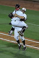 Catcher Kevin Martir (32) of the Maryland Terrapins jumps into the arms of closer Kevin Mooney after a game-ending double play to defeat the South Carolina Gamecocks 4-3 in an NCAA Division I Baseball Regional Tournament game on Saturday, May 31, 2014, at Carolina Stadium in Columbia, South Carolina. Maryland won, 4-3. (Tom Priddy/Four Seam Images)