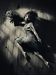 Young woman in a dress with a bouquet of wild flowers in a dynamic leap on wooden floor background, abstract artistic portrait in dramatic dim light black and white in vintage tones Image © MaximImages, License at https://www.maximimages.com