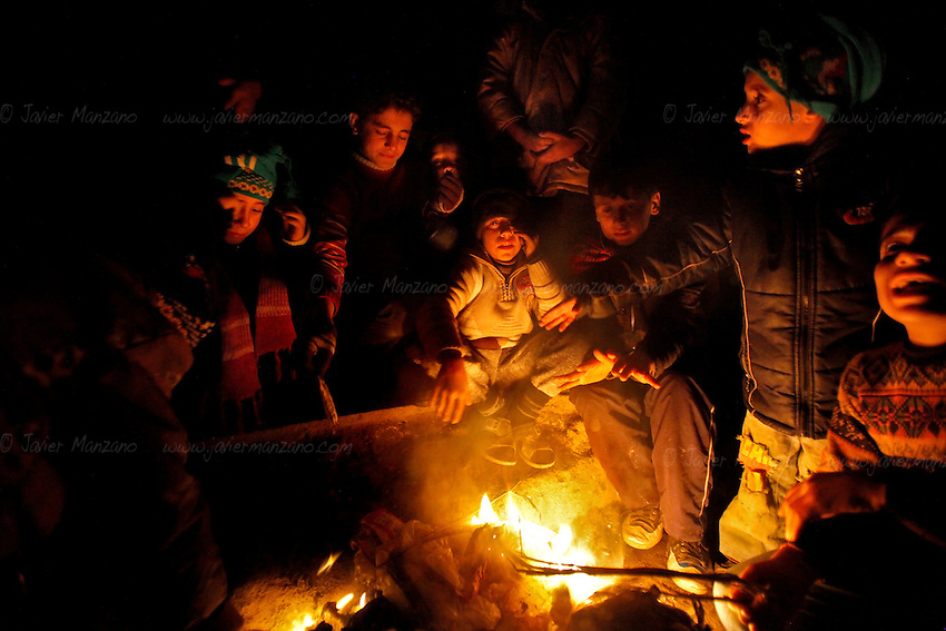 Children burn trash to provide heat next to the line of people waiting outside a bakery in the Shaar neighborhood of Aleppo. This fire is the only light that glow at night in this opposition neighborhood - electricity was cut ten days ago leaving people without the means to heat their homes as the temperatures drop in the early days of December.<br /> <br /> It was midnight when most people waiting in line lost hope and began to walk home. No benzine, no bread.<br /> <br /> 12/05/2012 - Shaar neighborhoo, Aleppo, Syria...©Javier Manzano