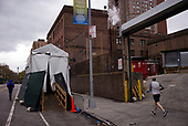 April 18, 2020<br /> Brooklyn, New York<br /> Fort Greene<br /> <br /> The Brooklyn Hospital Center with its white cooler trailer set outside to use as a morgue for those who died from the crononavirus. Pedestrians pass by as it has become a part of everyday life in the New York.