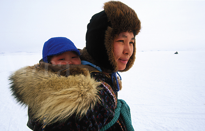 Portrait of a Native Alaskan woman wearing a fur hat and traditional coat, with an infant tucked within. Alaska.
