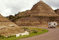 AJ3540, Theodore Roosevelt National Park, RV, South Unit, North Dakota, vacation, travel, road, rock formation, A recreational vehicle travels along the scenic loop drive as it winds through colored rock formations of Theodore Roosevelt National Park in the South Unit in the state of North Dakota.