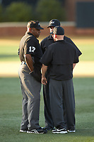 Home plate umpire Gregory Street (left) confers with first base umpire Joseph Holt (right) and third base umpire Brad Newton (center) during the NCAA baseball game between the Liberty Flames and the Wake Forest Demon Deacons at David F. Couch Ballpark on April 25, 2018 in  Winston-Salem, North Carolina.  The Demon Deacons defeated the Flames 8-7.  (Brian Westerholt/Four Seam Images)