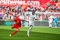 Nathaniel Clyne of Liverpool  takes a tumble while Modou Barrow of Swansea City  chases the ball during the Premier League match between Swansea City and Liverpool at The Liberty Stadium on October 1, 2016 in Swansea, Wales.
