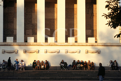 Sofia, Bulgaria. People sitting on a wall next to a large institutional building.