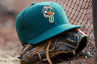 A Greensboro Grasshoppers cap sits on top of a glove in the visitors dugout at  L.P. Frans Stadium July 10, 2010, in Hickory, North Carolina.  Photo by Brian Westerholt / Four Seam Images