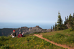 Two hikers rest amid wildflowers along the Elwa Trail, above the Hurricane Ridge area, Olympic National Park, Olympic Penninsula, Washington.  The view north extends over the Strait of Juan de Fuca to Vancouver Island, Canada.  Outdoor Adventure. Olympic Peninsula