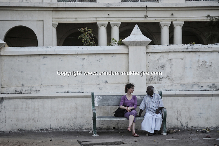 A western tourist talks to a local person sitting on a bench at Goubert Avenue in Pondicherry. Arindam Mukherjee.