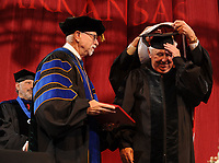 NWA Democrat-Gazette/ANDY SHUPE<br /> William Dillard (right) holds onto his mortar board Saturday, May 13, 2017, as Ben Hyneman (back), chair of the Board of Trustees of the University of Arkansas System, awards him with an honorary degree while Joseph Steinmetz (left), chancellor, looks on during commencement exercises in Bud Walton Arena in Fayetteville. Visit nwadg.com/photos to see more photographs from the ceremony.