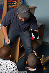 Preschool 3-4 year olds male teacher in training playing with group of boys in block area using puppet