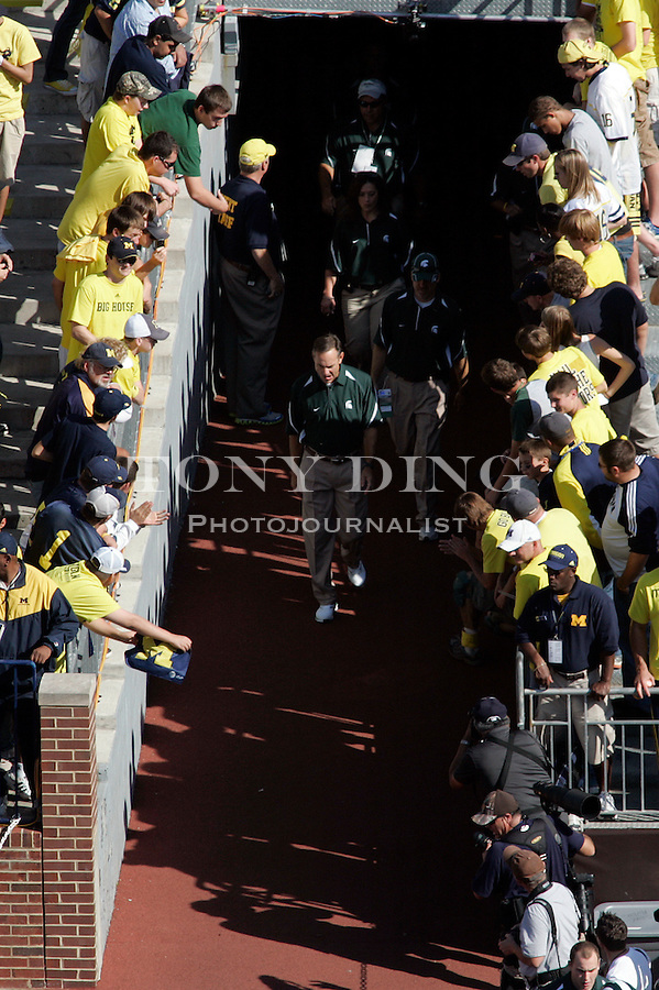 Michigan State head coach Mark Dantonio, center, walk into Michigan Stadium before an NCAA college football game with Michigan, Saturday, Oct. 9, 2010, in Ann Arbor, Mich. Dantonio is coaching his team from the press box during the game. (AP Photo/Tony Ding)