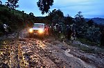 IIn rainy season, stuck in the mud at dusk in the mud on a mountain road in the western tea region of Rwanda. Villagers arrive to negotiate their services for giving us a needed push.