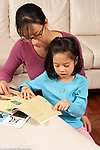 8 year old girl at home doing homework for Chinese language class, mother assisting her
