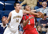11 November 2009:  Max Zhang of California tries to block Eli Holman of Detroit from getting a loose ball during the game at Haas Pavilion in Berkeley, California.   California defeated Detroit, 95-61.