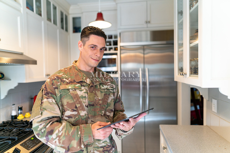 Off duty US soldier in uniform at home in his kitchen on the computer, for sale as stock photography