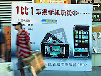 A man passes an advertising billboard for iphone in Guangzhou, China. The financial crisis won't have too much impact on Chinese consuming market. According to a survey by Nielsen of 50 countries and regions, only 35 percent of Chinese people believed the domestic economy was in a contraction. The figure was the lowest among the 50 world markets..