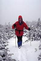 Winter hiker navigating through a snow storm in the White Mountains of New Hampshire, nearing the summit of Mt. Clinton. Bill McDonald. Mt. Clinton NH USA White Mountains.