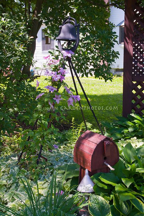Bird house, climbing pink Clematis vine, ornamental garden bell, shde, house, under the tree, hostas