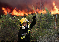 Pictured: A fireman gets people to move on.<br /> Re: A forest fire has been raging in the area of Kalamos, 20 miles east of Athens in Greece. There have been power cuts, country houses burned and children camps evacuated from the area.
