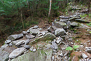 Mt Tecumseh Trail in the New Hampshire White Mountains. At the time of this photo in July 2012 (less than two months after this staircase was built), the stonework appeared to be not holding up. In August 2012, the stones were re-positioned and removed from the footbed of the staircase.