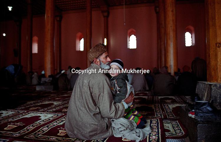 A Kashmiri Muslim with his grandson at world famous Jamia Mosque at Srinagar, Kashmir Valley, India