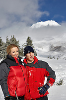 Man and woman near Timberline Lodge in winter with Mt. Hood.Oregon