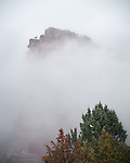 Emerging.  This photo of Castle Rock (captured right outside my patio door) is from day 1 of a three day winter storm.  The precipitation was still in the form of rain at this point, though it changed to snow later on.  But the clouds were low enough to make for some dramatic views of our famous Sedona red rocks.<br /> <br /> Tech info: Nikon D850 camera with Nikon 28-300mm lens at 250mm, 1/100 sec. at f8, ISO 1000.<br /> <br /> Image ©2021 James D. Peterson