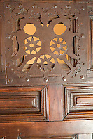 A detail of a iron-work panel in a carved wooden door