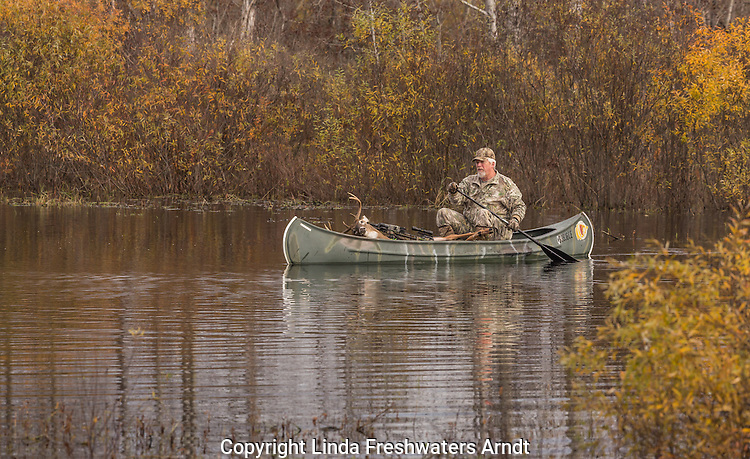 Crossbow hunter returning in a canoe with his 8-point white-tailed buck.