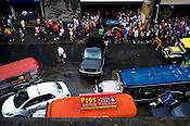 Traffic moves slowly and the crowds gather by the side of the road as the streets are clogged after the rain in Manila, the capital of Philippines. Photo: Sanjit Das