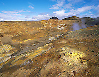 Geothermal landscape with sulphur-stained earth, steaming and fumes and distant low hills at Myvatn, northern Iceland