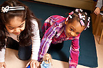 Education Preschool two girls playing together pushing car with small dolls in them