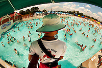 A lifeguard watches over swimmers in the 20-acre Boomerang Bay water park at Carowinds theme Park near Charlotte, NC. Seen here is Bondi Beach, a 600,000-gallon, 34,000 square-foot wave pool that provides a fresh-water surf-like experience. The water attractions are part of Carowinds, a 112-acre theme park (amusement park) located on the state lines between North Carolina and South Carolina. The theme park is a popular summer Carolina attraction, one of three major theme parks in the Carolinas.