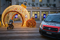 Switzerland. Canton Ticino. Lugano. Night time. Piazzetta San Carlo. Town center. An electrical ball is used in the street as Christmas decoration. A lonely baby boy seated in a stroller. A police (polizia) van is parked on the place. The Lugano branch of Julius Bär. Julius Bär Group AG, known alternatively as Julius Baer Group Ltd., is a small to medium sized generalist private banking corporation founded and based in Switzerland. It is among the older Swiss banking institutions. 23.12.2020 © 2020 Didier Ruef