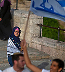 A Muslim woman looks at Israelis dance and wave flags outside Damascus gate in Jerusalem Wednesday May 28 2014, during festivities marking Jerusalem day. The Day marks the reunification of Jerusalem following the 1967 Six Day War when Israel captured the Arab part of the city from Jordan. Photo By Eyal Warshavsky