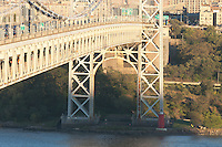 The George Washington Bridge and evening traffic high over Jeffrey's Hook Lighthouse on the Hudson River