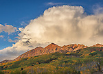 Gunnison National Forest, CO: Storm cloud in afternoon light over the Ruby Range with early fall colors on aspen hillsides