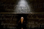 University of Wisconsin-Madison senior Guilia Rocca, who is fluent in Italian, Chinese, French and English, poses in front of a chalk board with ?the importance of language? written in various languages for a portrait series about individuals and their beliefs.
