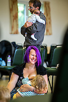 """Breastfeeding a toddler at a singing and signing group whilst talking to the other mothers. The woman's husband cuddles their new born baby in the background.Image from the breastfeeding collection of the """"We Do It In Public"""" documentary photography picture library project: <br />  www.breastfeedinginpublic.co.uk<br /> <br /> <br /> Berkshire, England, UK<br /> 27/09/2013<br /> <br /> © Paul Carter / wdiip.co.uk"""