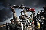© Remi OCHLIK/IP3 -   RAS LANOUF March 11, 2011 - Rebel fighters sing and celebrate..Opposition forces fight troops of colonel Muamar Gadhafi on a road just outside the strategic oil town of Ras Lanouf, Libya..Loyalist forces bombed the rebels from the air and the ground. At least five oppositin fighters were killed and fifteen injured